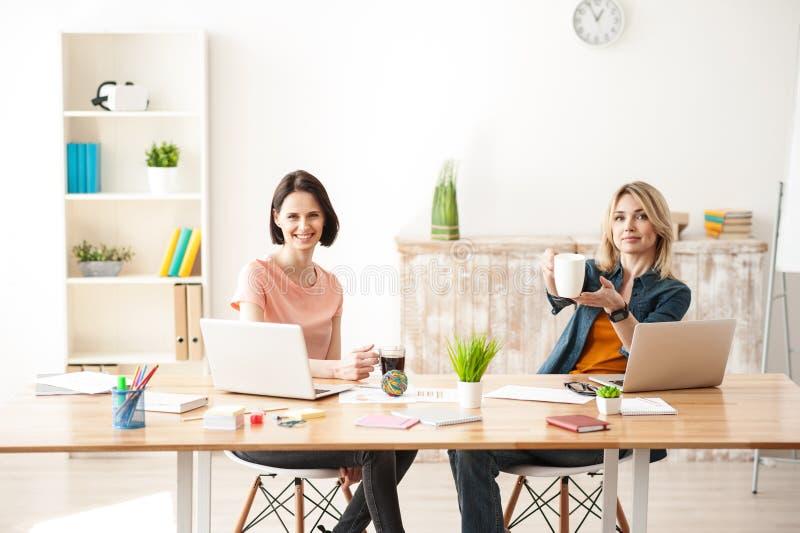 Nette zwei weibliche Kollegen haben einen Rest stockfotografie