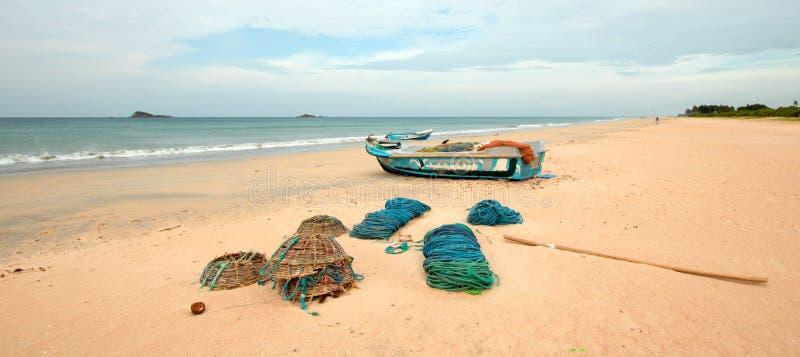 Netten, vallen, manden, en kabels naast vissersboot op Nilaveli-strand in Trincomalee Sri Lanka stock fotografie