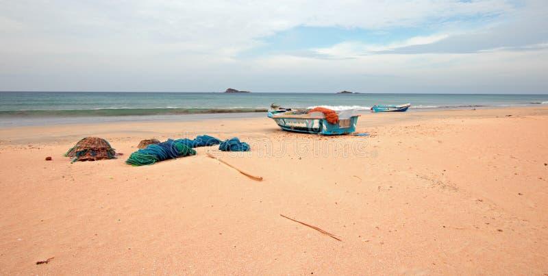 Netten, vallen, manden, en kabels naast vissersboot op Nilaveli-strand in Trincomalee Sri Lanka royalty-vrije stock afbeeldingen