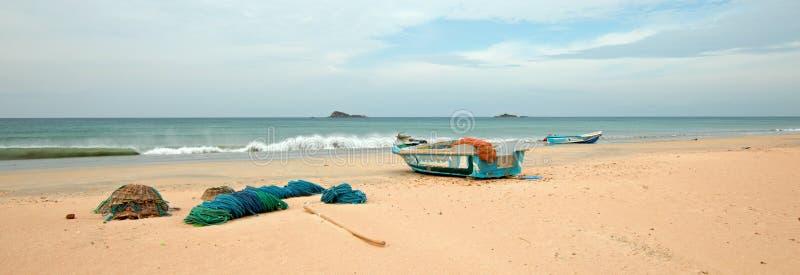 Netten, vallen, manden, en kabels naast vissersboot op Nilaveli-strand in Trincomalee Sri Lanka royalty-vrije stock foto