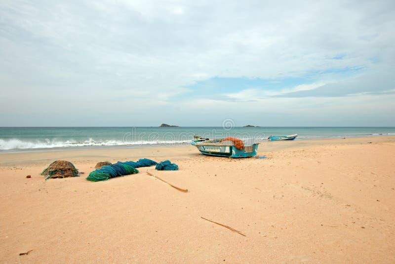 Netten, vallen, manden, en kabels naast vissersboot op Nilaveli-strand in Trincomalee Sri Lanka royalty-vrije stock fotografie