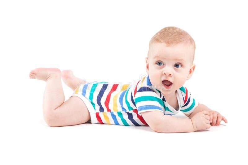 Netter überraschter kleiner Junge im bunten Hemd liegt auf Bauch lizenzfreies stockfoto