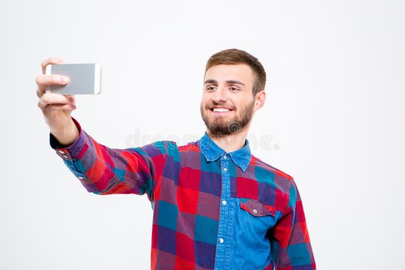 Netter überzeugter junger Mann, der selfie unter Verwendung des Handys nimmt lizenzfreie stockbilder