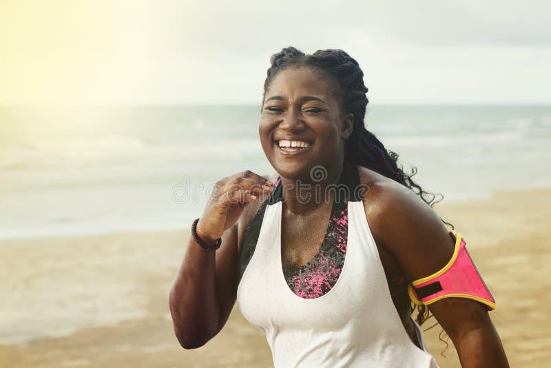 Netter afrikanischer Läufer, der während Trainings des im Freien auf Strand rüttelt lizenzfreie stockbilder