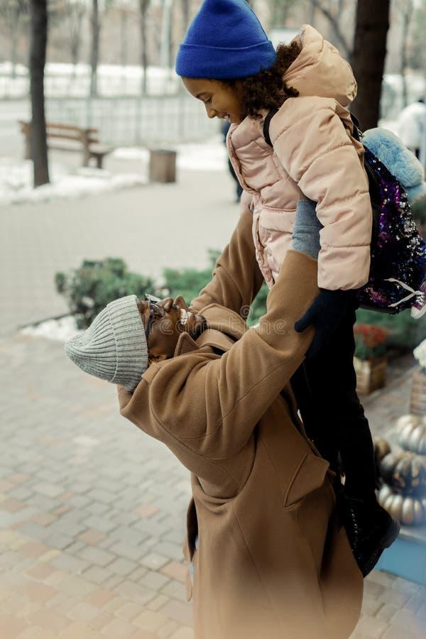 Netter afro-amerikanischer Vater, welche glücklicher Sitzung sein kleines Mädchen glaubt lizenzfreie stockfotografie