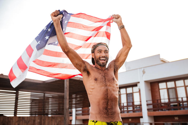 Netter Afroamerikanermann, der Flagge von Vereinigten Staaten hält lizenzfreies stockbild
