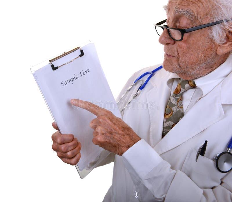Netter alter Doktor, der auf Diagramm zeigt stockbild