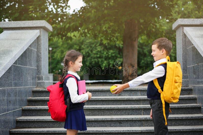 Netter Angebotapfel des Schuljungen zum Mädchen mit Briefpapier stockfoto