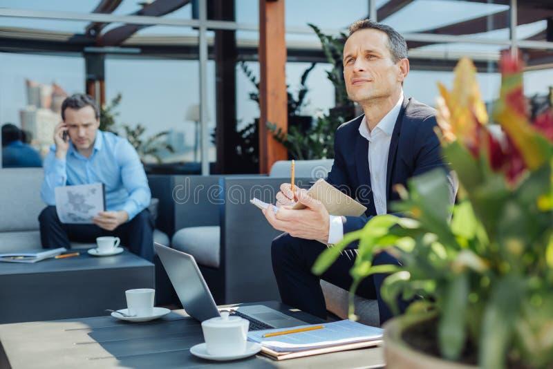 Netter angenehmer Unternehmer, der hinunter seine Ideen merkt stockfotos