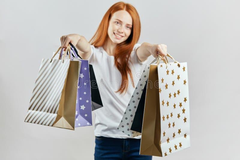 Netter angenehmer Verkäufer bietet Einkaufstaschen Leuten an stockbilder