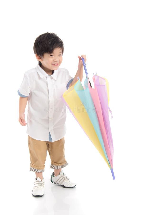 Netter asiatischer Junge, der Regenschirm hält lizenzfreie stockfotos