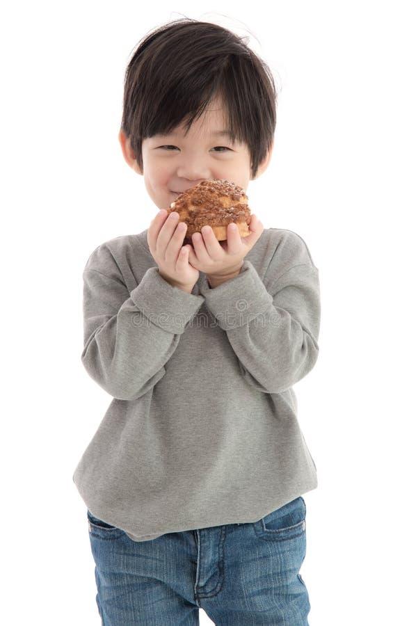 Netter asiatischer Junge, der Windbeutel isst stockfotos