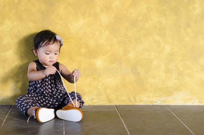 Netter asiatischer Kleinkindversuch zur Bindung/tragen ihre eigenen braunen Schuhe stockfotos
