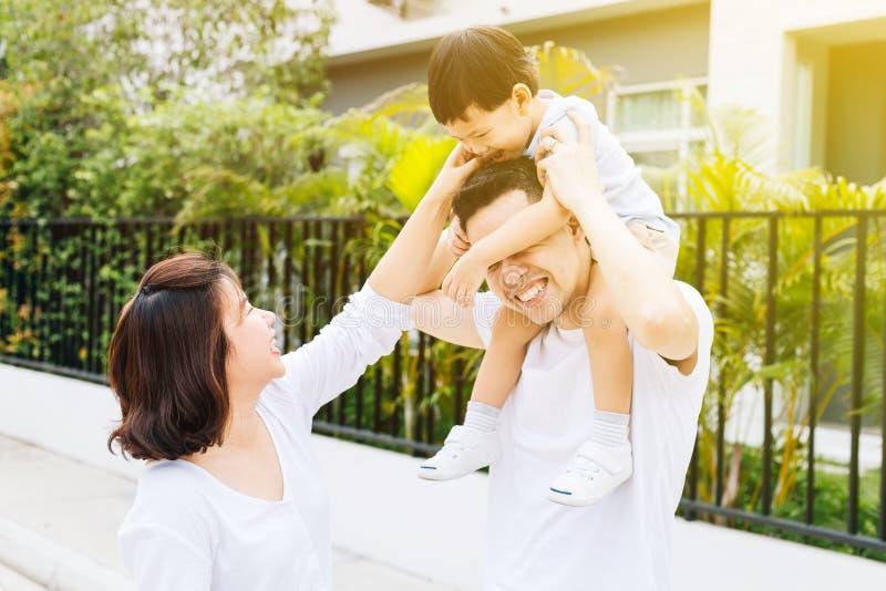 Netter asiatischer Vater, der seinen Sohn zusammen mit seiner Frau im Park piggbacking ist Aufgeregte Familie, die Zeit zusammen  stockfotos