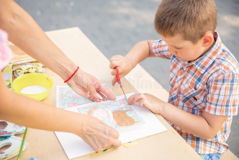 Netter Ausschnitt des kleinen Jungen formt aus farbigem Papier heraus Seiend kreative, sich entwickelnde Fantasie, Kreativität, t lizenzfreies stockbild