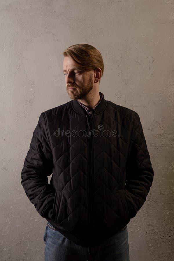 Netter bärtiger Mann von mittlerem Alter in einer schwarzen Jacke und in den Jeans steht hinter der Wand, die weg schaut stockfoto