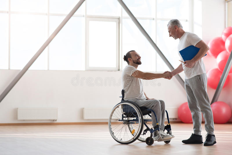 Netter behinderter Patient, der seinen körperlichen Therapeuten in der Turnhalle grüßt stockbild