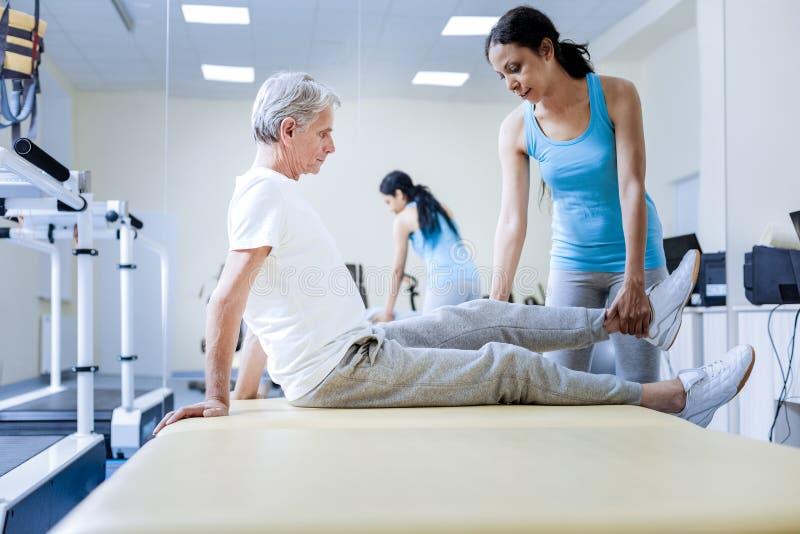 Netter Berufstrainer, der die verletzten Muskeln ihres gealterten Patienten wärmt stockfoto