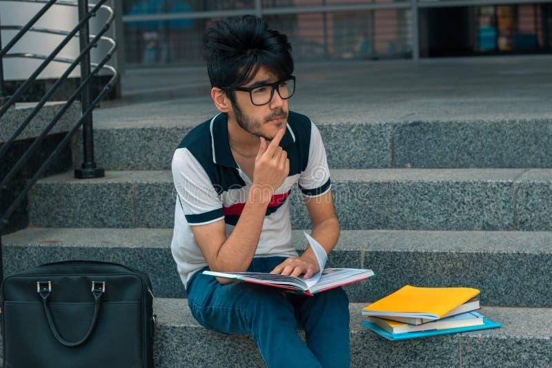 Netter beunruhigender Student sitzt mit Büchern lizenzfreies stockfoto