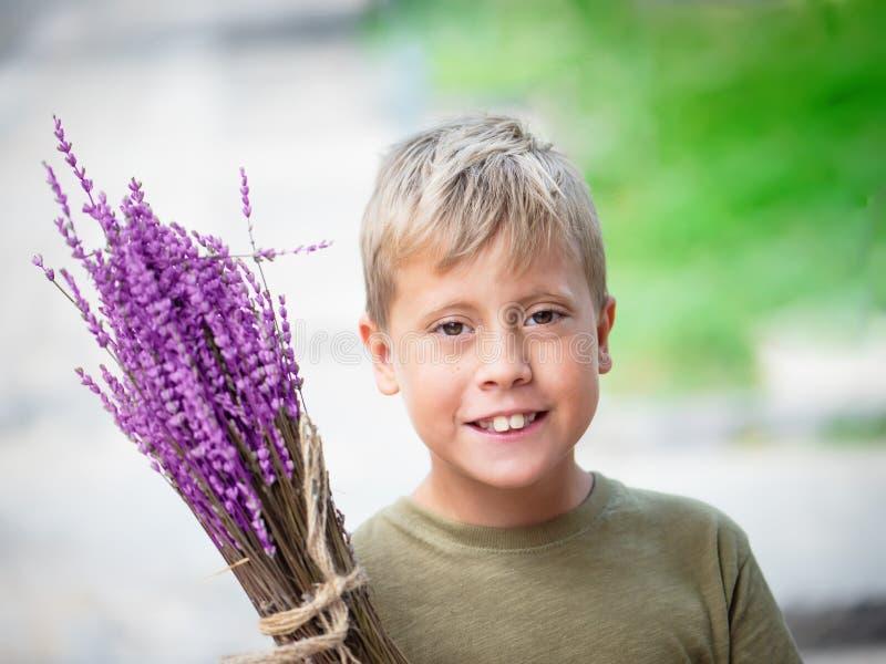 Netter blonder Junge mit Lavendel in den Händen lizenzfreie stockfotos