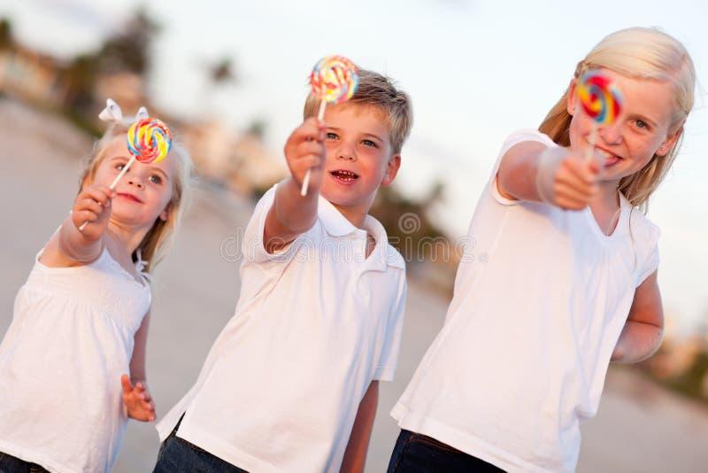 Netter Bruder und Schwestern, die draußen ihre Lutscher genießen lizenzfreie stockbilder