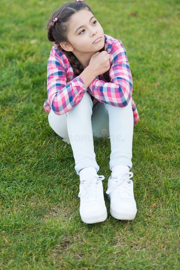 netter Daydreamer Mädchenkleinkind Freizeit im Park draußen aufwenden Mädchen sitzen auf Gras im Park Kind genießen den sonnigen  lizenzfreie stockfotos