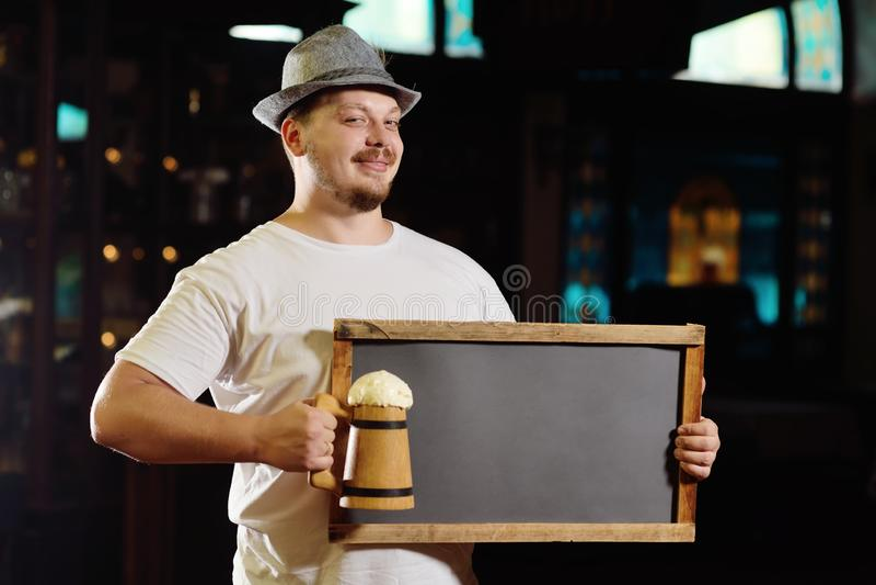 Netter netter dicker Mann in einem bayerischen Hut, der eine Tafel oder eine Platte auf dem Hintergrund einer Kneipe hält stockfotos