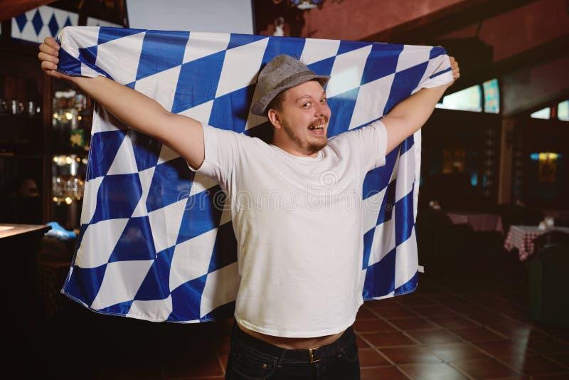 Netter dicker Mann mit einem dicken Bauch mit einer oktoberfest Flagge und einem bayerischen Hut lizenzfreie stockfotos