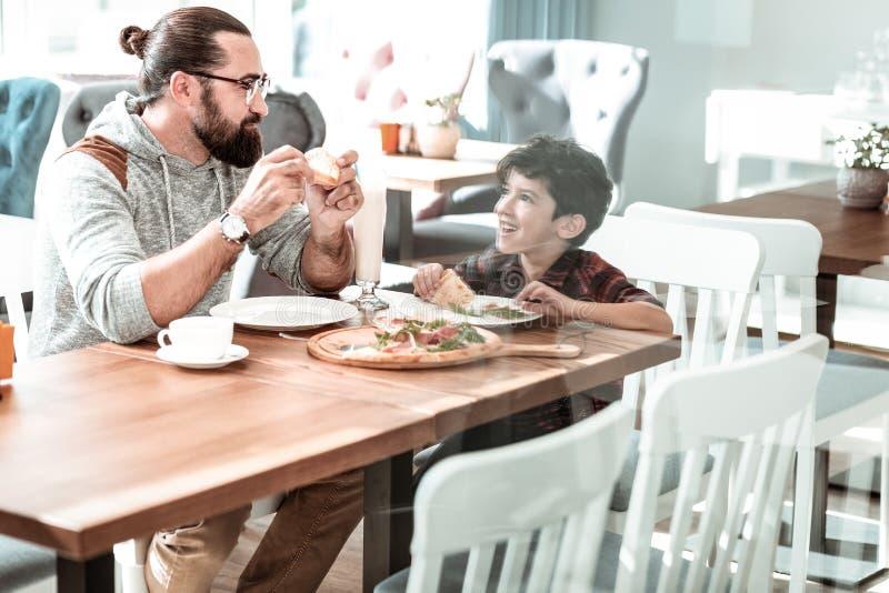 Netter dunkeläugiger kleiner Junge, der seinen Vater aufpasst, Pizza zu essen stockfoto