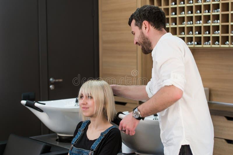 Netter dunkelhaariger Mann, der Frisur für jugendlich blondes Mädchen im Frisurnsaal tut lizenzfreie stockfotografie