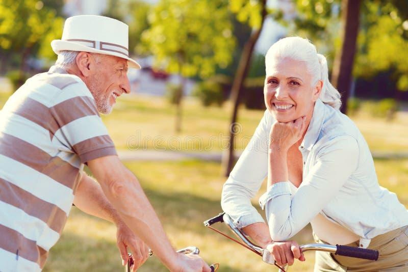 Netter Ehemann und Frau, die Pause nachdem dem Radfahren in Park macht stockbild