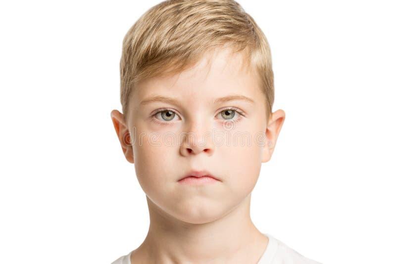 Netter ernster Junge mit den großen blauen Augen, lokalisiert auf weißem Hintergrund stockbild