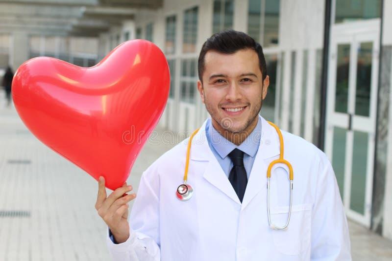 Netter ethnischer Doktor mit einem geformten Ballon des Herzens stockfotografie