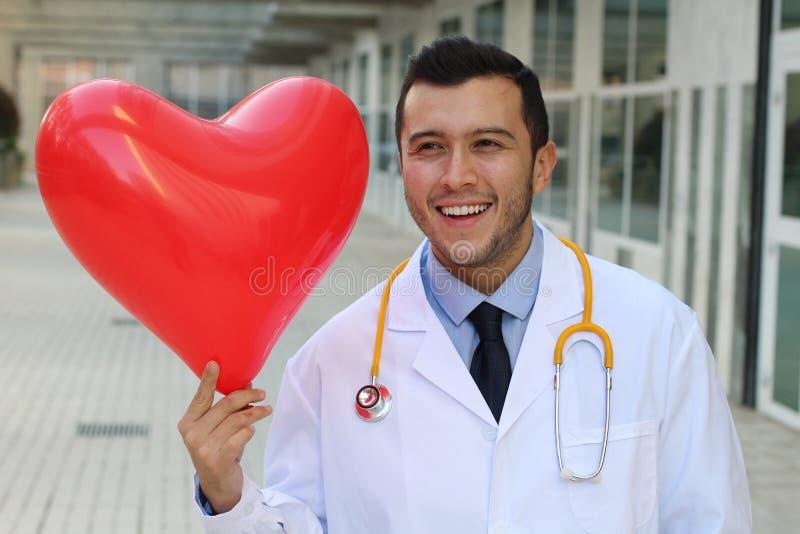 Netter ethnischer Doktor mit einem geformten Ballon des Herzens lizenzfreies stockbild
