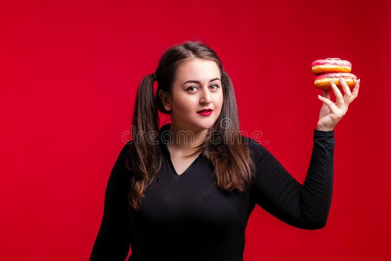 Netter fetter Brunette hat den Spaß, der mit köstlichen Schaumgummiringen aufwirft plus lizenzfreies stockfoto