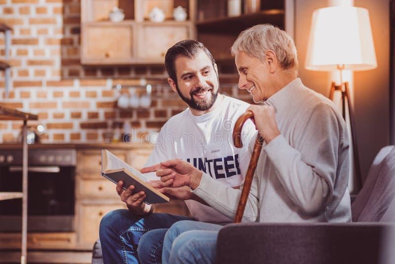 Netter Freiwilliger, der ein Buch für einen Pensionär liest stockfotos