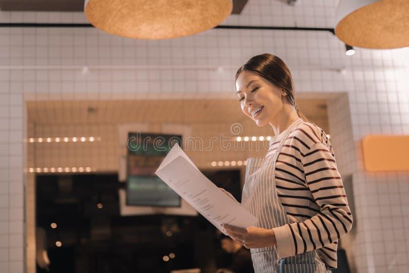 Netter Gastfreundschaftsmanager, der das Menü des neuen Restaurants studiert lizenzfreie stockfotos