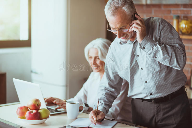 Netter gealterter Mann, der am intelligenten Telefon spricht stockfotos