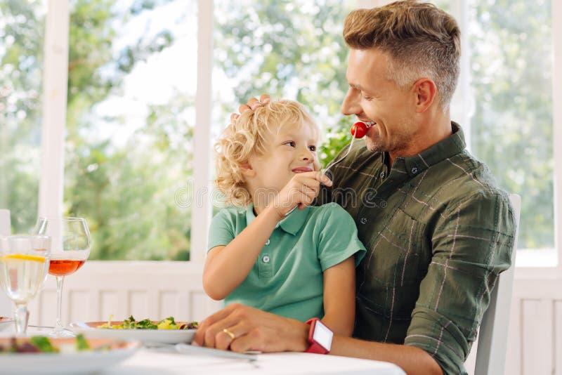 Netter gelockter blond-haariger Sohn, der seinem Vater Tomate gibt stockfotos