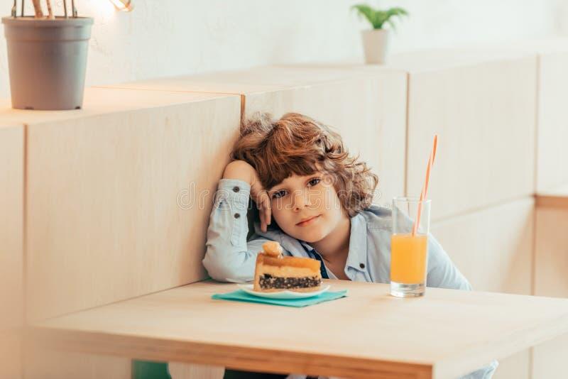 netter netter gelockter Junge, der im Café mit Stück des Kuchens sitzt stockfoto