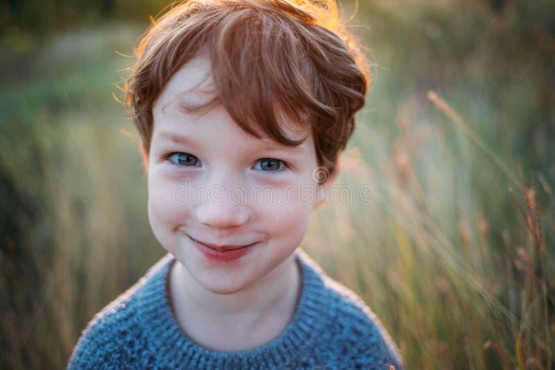 Netter gelockter Junge, ein schlauer Blick auf die Kamera, Nahaufnahmeporträt stockfotografie