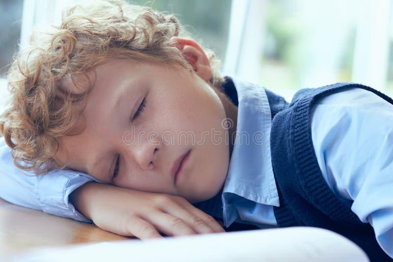 Netter gelockter müder und erschöpfter einschlafender Grundschulestudent beim Studieren stockbild