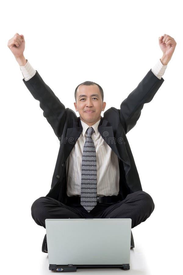 Netter Geschäftsmann, der auf dem Boden sitzt stockfoto