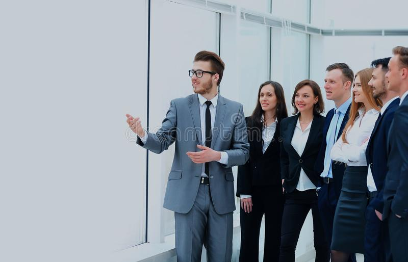 Netter Geschäftsmann, der ein neues Geschäftsprojekt mit den Mitgliedern seines Teams bespricht stockfotografie