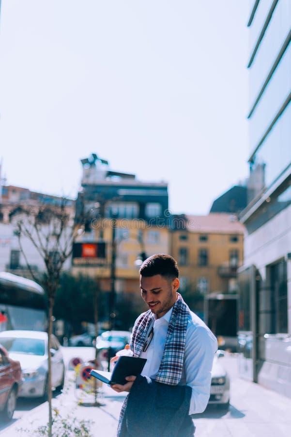 Netter Geschäftsmann hat Spaß beim Trinken seines Kaffees auf der Straße lizenzfreie stockbilder