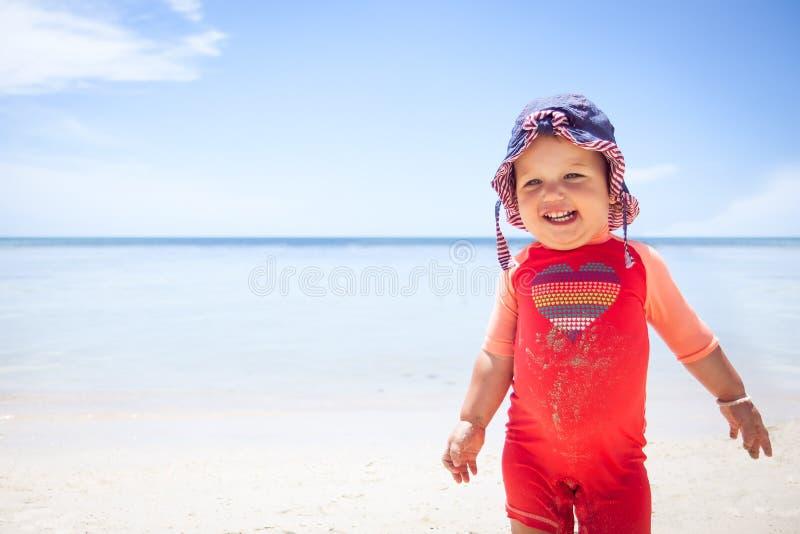 Netter netter glücklicher lächelnder Himmellichtschutzhintergrund-Kopienraum des Babykindersonnenschutzanzugstrandes blauer See stockbilder