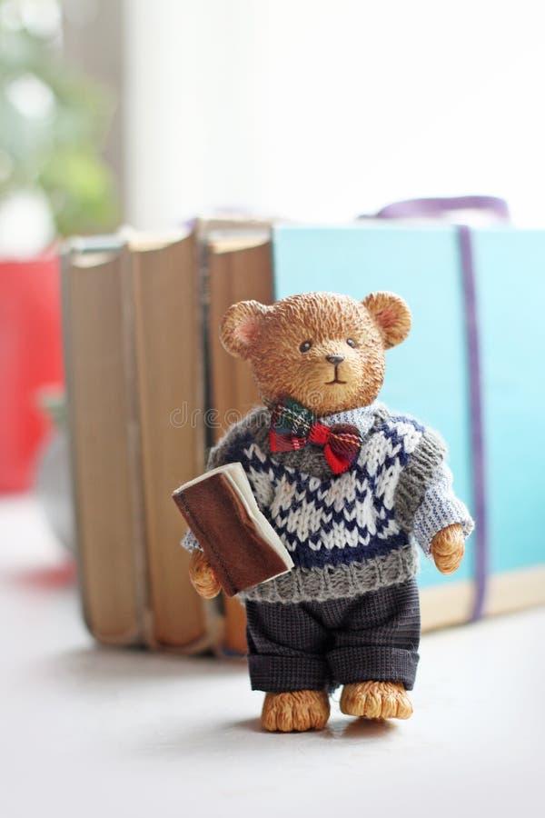 Netter glücklicher Teddy Bear mit Buch keramischen Modellen lizenzfreie stockfotos