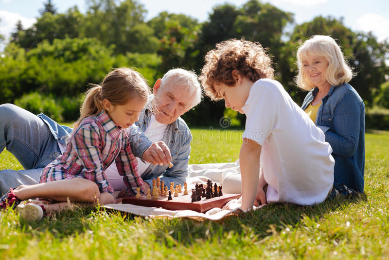 Netter Großvater, welche seiner Enkelin hilft, Schach zu spielen lizenzfreie stockfotografie