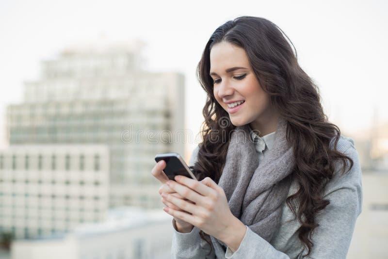 Netter hübscher Brunette im Winter kleidet das Senden eines Textes auf ihr stockfotos