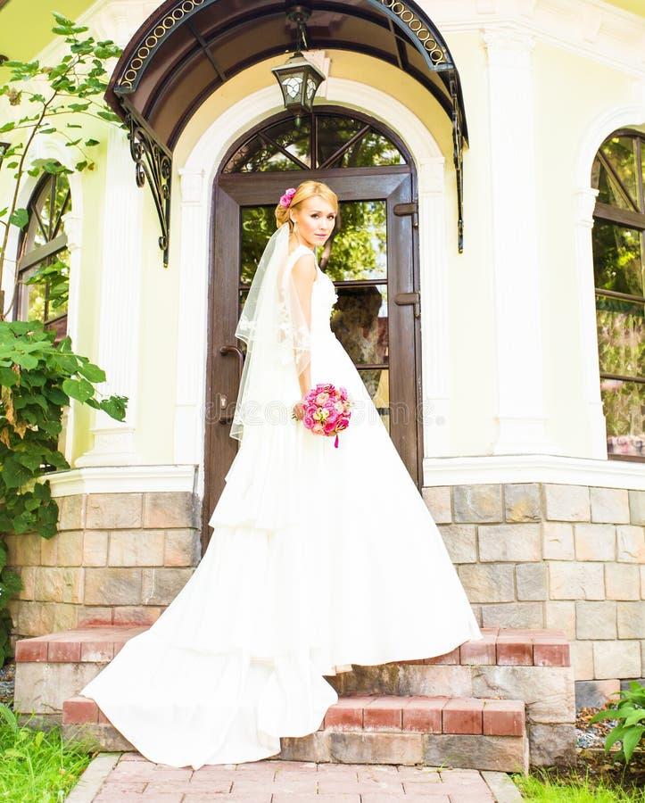 Netter Hochzeitsblumenstrauß in der Hand der Braut lizenzfreie stockbilder